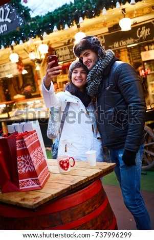 Happy loving couple making self portrait at christmas fair outdoors, smiling happy, embracing.