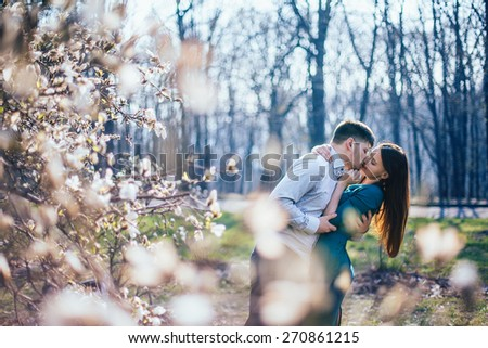 Happy loving couple. Portrait of beautiful young couple kissing outdoors in magnolia flowers blossom. - stock photo