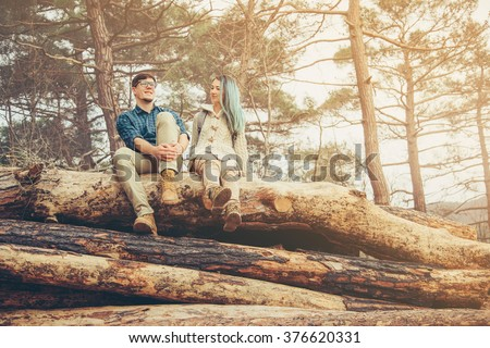 Happy loving couple sitting on fallen tree trunk in the forest at sunny day - stock photo