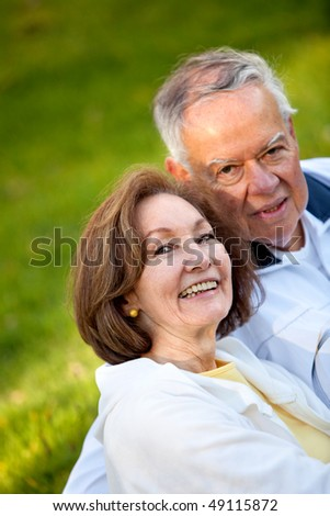 Happy loving couple sitting outdoors and smiling
