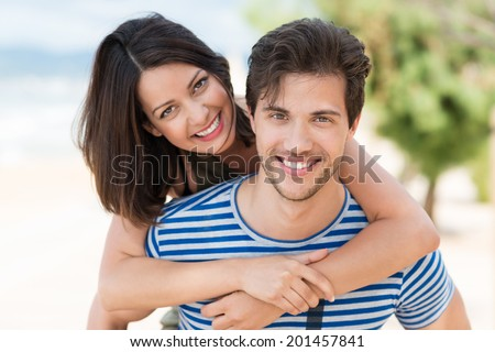 Happy loving couple smiling with pleasure as they enjoy a hot summer day on a tropical beach with the woman hugging the man from behind as they smile at the camera - stock photo