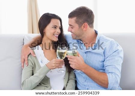 Happy loving couple toasting wine glasses at home - stock photo