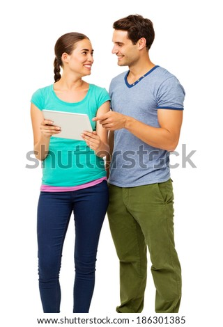 Happy loving couple using tablet PC isolated over white background. Vertical shot. - stock photo