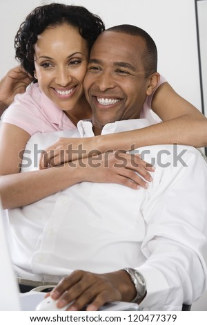 Happy loving couple with man using computer - stock photo