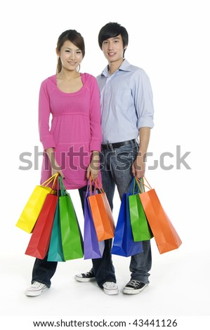 Happy loving couple with shopping bags smiling - stock photo