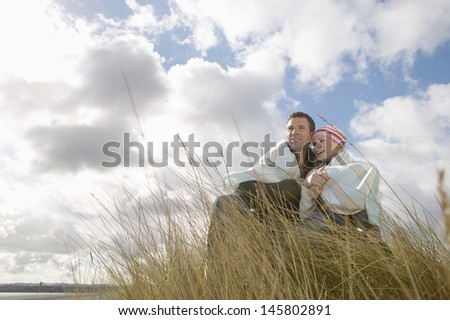 Happy loving couple wrapped in blanket against cloudy sky - stock photo