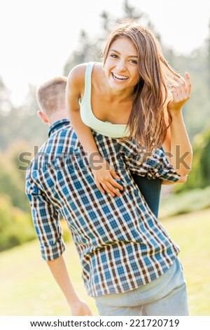 Happy loving couple. Young man holding beautiful cheerful girl on his shoulder - stock photo