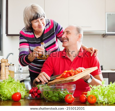happy loving elderly couple cooking with tomatoes in home kitchen