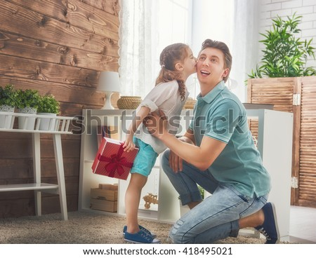 Happy loving family and Father's Day. Father and his daughter. Cute child girl kisses dad and gives him a gift. - stock photo