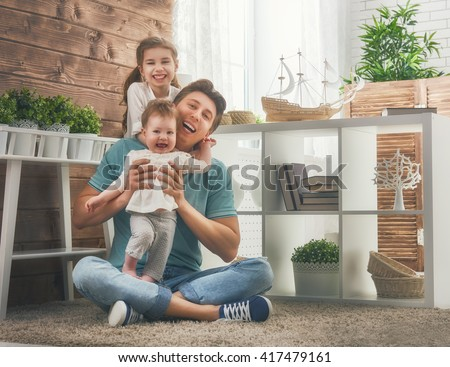 Happy loving family and Father's Day. Father and his daughters children girls playing and hugging.  - stock photo