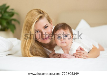 Happy loving family concept. Beautiful mother playing with her baby girl in the bedroom. They smiling and hugging together on white bed linens