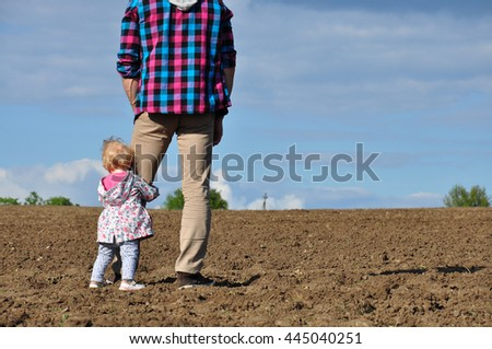 Happy loving family. Father and his daughter child girl playing and hugging outdoors in the field. Cute little girl hugs daddy. Concept of Father's day. - stock photo