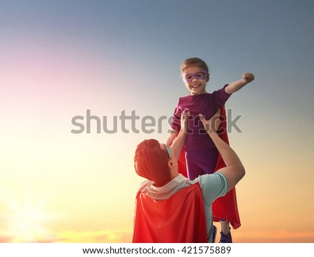 Happy loving family. Father and his daughter child girl playing outdoors. Daddy and her child girl in an Superhero's costumes. Concept of Father's day. - stock photo