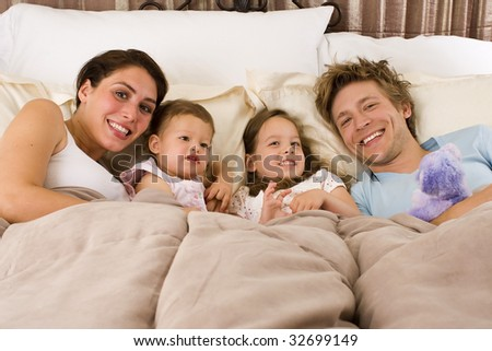 Happy loving family laying in bed - stock photo