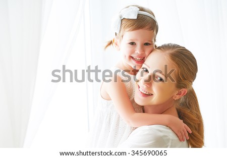 Happy loving family. mother and child girl kissing and hugging