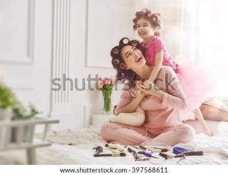Happy loving family. Mother and daughter are doing hair and having fun. Mother and her child girl playing and hugging. - stock photo
