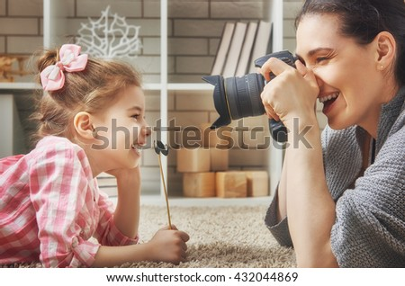 Happy loving family. Mother and her daughter child girl playing and making photo. - stock photo