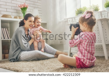 Happy loving family. Mother and her daughters children girls playing and making photo. - stock photo