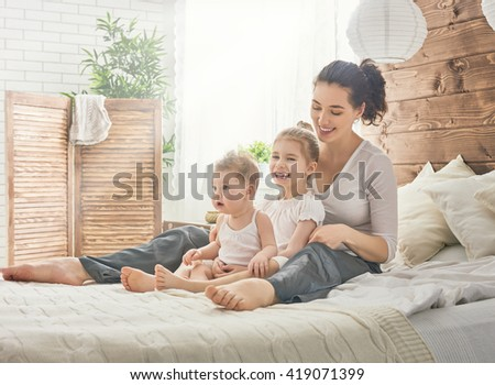 Happy loving family. Mother and her daughters children girls playing in bed. - stock photo