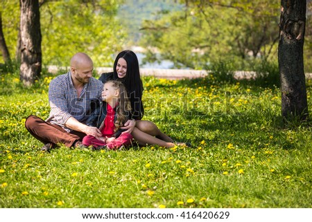 Happy loving family on flowery lawn in springtime