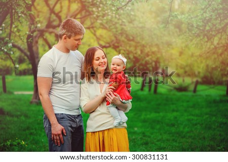 happy loving family on the walk with baby daughter in summer park - stock photo