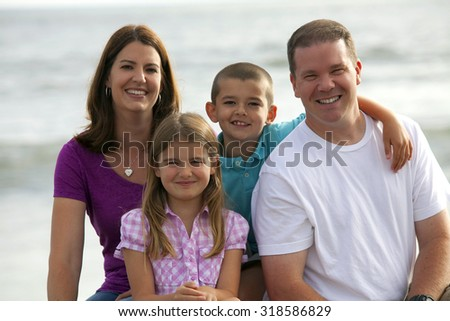 Happy loving family playing on the beach - stock photo