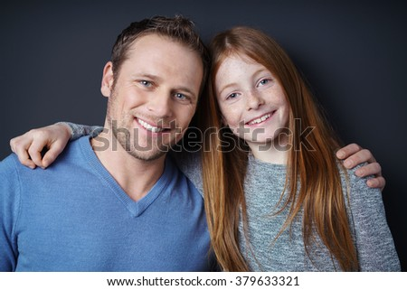 Happy loving father and his little daughter posing arm in arm grinning happily at the camera, head and shoulders portrait - stock photo