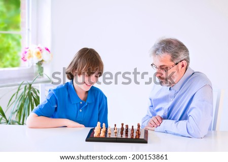 Happy loving grandfather enjoying a day with his grandson, laughing school age boy, playing chess in a white dining room with a window - stock photo