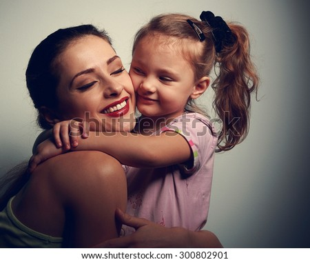 Happy loving mother and kid girl hugging on dark shadows background. Closeup portrait of happiness - stock photo
