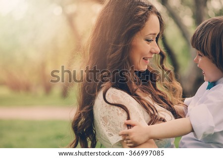happy loving mother with toddler son on the walk in sunny park. Family spending time together in spring or summer. Cozy warm mood. - stock photo