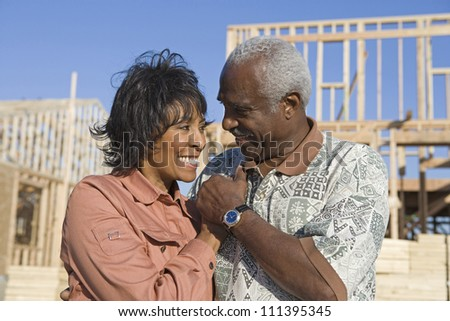 Happy loving senior African American couple in front of incomplete house - stock photo