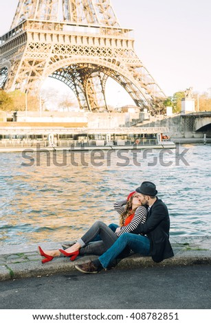 Happy loving stereotypical french couple having fun on a date, hugging and sitting near the Seine River under the Eiffel Tower in Paris, France - stock photo