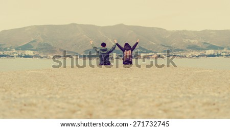 Happy loving traveler couple sitting on pier at bay in front of mountains and town. Space for text in lower part of image. Image with instagram color - stock photo
