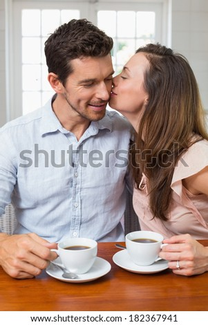 Happy loving young couple with coffee cups sitting at home - stock photo