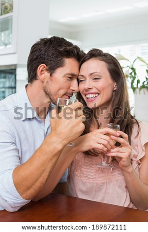 Happy loving young couple with wine glasses at home - stock photo