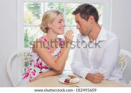 Happy loving young woman feeding man pastry at dining table at home - stock photo