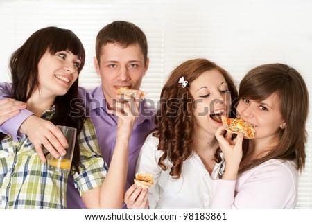 Happy luck Caucasian campaign of four people eating pizza on a light background