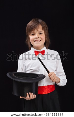 Happy magician boy on black background - with magic wand and hat - stock photo