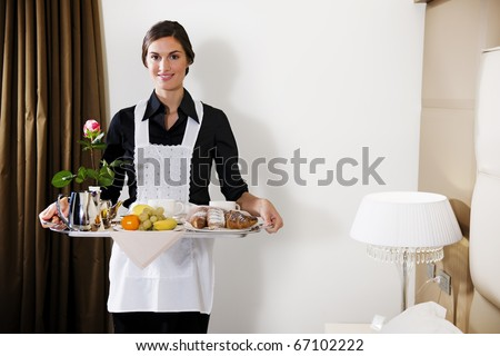 Happy Maid Carrying Breakfast Tray - stock photo