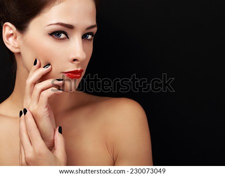 Happy makeup woman looking with red lips and black fingers on black background - stock photo