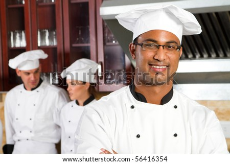 happy male african professional chefs in industrial kitchen with colleagues behind - stock photo
