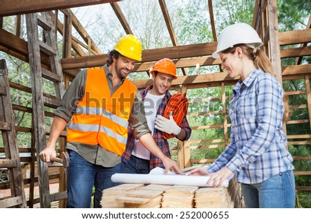 Happy male and female architects analyzing blueprint in wooden cabin at site - stock photo
