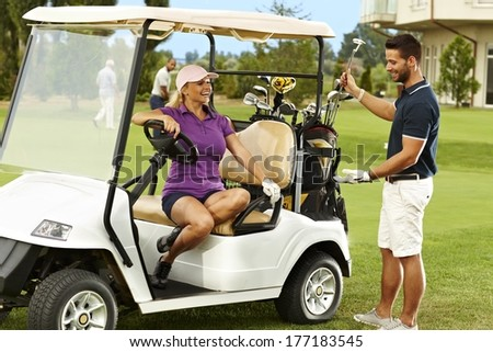 Happy male and female golfers talking on the fairway in golf cart. - stock photo