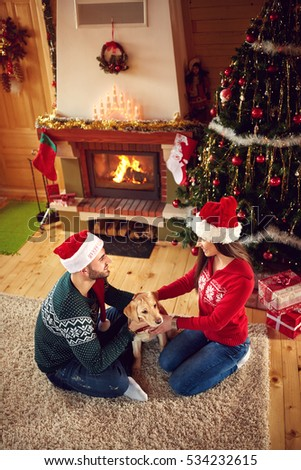 Happy male and female with dog at Christmas