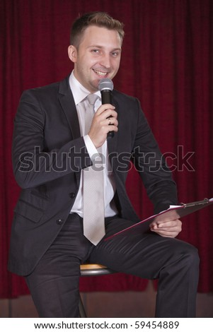 happy male announcer with microphone on stage - stock photo
