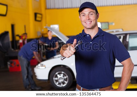 happy male auto mechanic giving thumb up holding wrench - stock photo