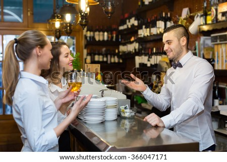 Happy male bartender and two smiling girls with wine at bar. Selective focus on guy - stock photo
