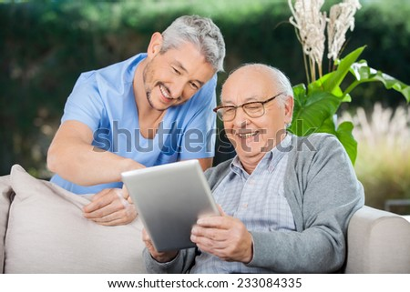 Happy male caretaker and senior man using tablet PC at nursing home porch - stock photo