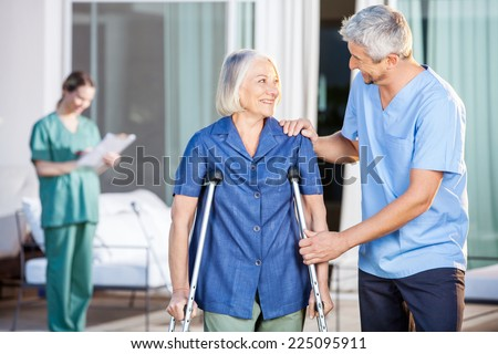 Happy male caretaker helping senior woman in walking with nurse in background at nursing home yard - stock photo