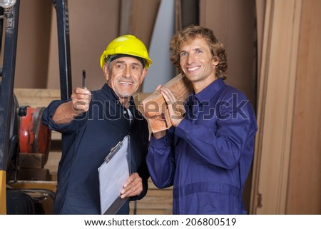 Happy male carpenter showing something to coworker carrying wooden planks in workshop - stock photo